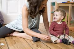 Germany, Berlin, Mother and son (2-3) sitting on wooden floor, laughing, Stock Photos