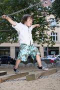 Germany, Berlin, Boy (3-4) at playground on suspension bridge Stock Photos
