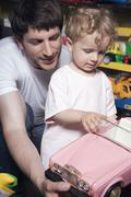 Germany, Berlin, Father and son (3-4) in toy store, portrait - stock photo