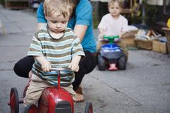 Stock Photo of Germany, Berlin, Mother and boy (2-3) (3-4) on toy tractor, close-up