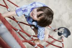 Germany, Berlin, Boy (3-4) at playground climbing on jungle gym, elevated view - stock photo