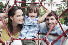 Stock Photo of Germany, Berlin, Family at playground looking through climbing net, portrait,