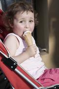 Germany, Berlin, Girl (3-4) in buggy eating icecream, side view, portrait Stock Photos