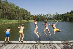 Italy, South Tyrol, Family jumping into lake Stock Photos
