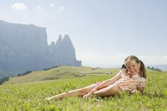Italy, South Tyrol, Seiseralm, Girl (7-7) lying in meadow, smiling, portrait - stock photo