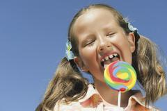 Italy, South Tyrol, Girl (6-7) licking lollypop, portrait, close-up Stock Photos