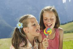 Italy, South Tyrol, Two girls (6-7) (10-11) licking lollypop, portrait, close-up - stock photo