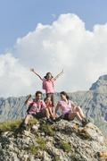 Stock Photo of Italy, South Tyrol, Family sitting on rock, cheering, portrait