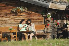 Italy, South Tyrol, Couple in front of log cabin drinking wine, portrait - stock photo