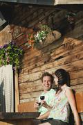 Italy, South Tyrol, Couple in front of log cabin holding wine glasses, smiling, - stock photo