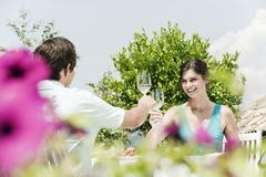Italy, South Tyrol, Couple in restaurant toasting with white wine, smiling Stock Photos