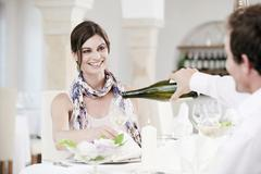 Couple in restaurant, man pouring wine into glass - stock photo