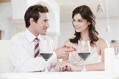 Couple sitting at table in restaurant, man holding gift parcel Stock Photos