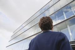 Germany, Hamburg, Businessman in front of office building, rear view Stock Photos