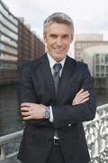 Germany, Hamburg, Businessman arms crossed smiling, portrait, close-up - stock photo