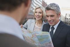 Germany, Hamburg, Business people holding city map, smiling, portrait - stock photo