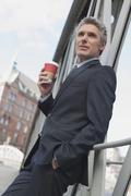 Germany, Hamburg, Businessman leaning on railing, holding mug of coffee Stock Photos
