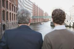 Germany, Hamburg, Two businessmen looking over canal, rear view Stock Photos