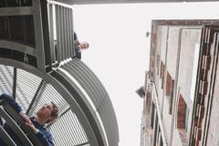 Stock Photo of Germany, Hamburg, Two Businessmen on platform of office building looking down,