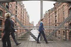 Germany, Hamburg, Business people crossing bridge - stock photo