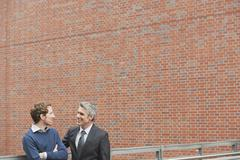 Germany, Hamburg, Two businessmen talking in front of brick wall - stock photo
