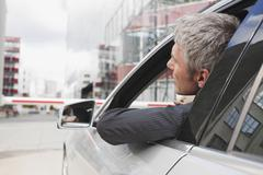 Germany, Hamburg, Businessman sitting in car in front of closed barrier - stock photo