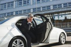 Germany, Hamburg, Businessman using mobile phone, leaving car, side view - stock photo