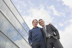 Germany, Hamburg, Two businessmen smiling, low angle view - stock photo