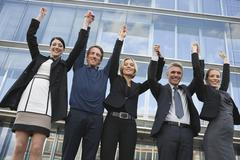 Germany, Hamburg, Five Business people cheering in front of office building Stock Photos