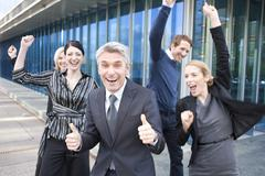 Germany, Hamburg, Five Business people cheering in front of office building - stock photo