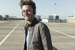 Germany, Berlin, Young man on parking level wearing headphones - stock photo