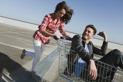 Germany, Berlin, Young woman pushing young man in shopping cart - stock photo