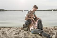 Germany, Berlin, Lake Wannsee, Young couple sitting on lakeshore, portrait Stock Photos