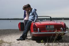 Stock Photo of Germany, Berlin, Lake Wannsee, Young couple standing by cabriolet, looking down