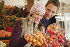 Stock Photo of Germany, Bavaria, Munich, Couple at Viktualienmarkt, woman holding berries