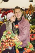 Germany, Bavaria, Munich, Couple at Viktualienmarkt, woman holding rose Stock Photos