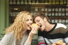 Germany, Bavaria, Munich, Young couple at Viktualienmarkt having snack, portrait Stock Photos