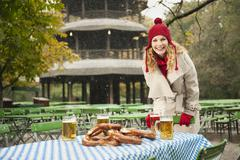 Germany, Bavaria, English Garden, Woman in beer garden - stock photo