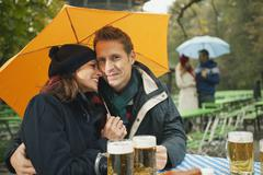 Germany, Bavaria, English Garden, Couple sitting in rainy beer Garden, holding - stock photo