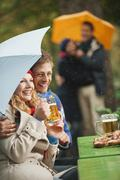 Germany, Bavaria, English Garden, Four persons in rainy beer garden, woman - stock photo