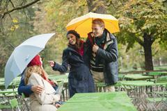 Germany, Bavaria, English Garden, Beer Garden, Four persons in rainy beer garden - stock photo