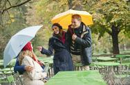 Stock Photo of Germany, Bavaria, English Garden, Beer Garden, Four persons in rainy beer garden