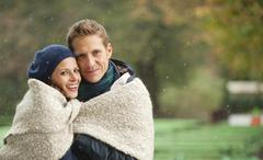 Germany, Bavaria, Munich, English Garden, Couple wrapped in blanket, portrait - stock photo