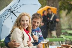 Stock Photo of Germany, Bavaria, English Garden, Beer Garden, Four persons in rainy beer