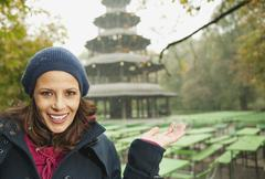 Germany, Bavaria, Munich, English Garden, Woman in beer garden, Chinese tower in - stock photo