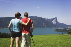 Austria, Lake Mondsee, Young couple looking at lake, rear view Stock Photos