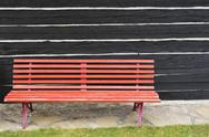 Stock Photo of Garden bench in front of wall