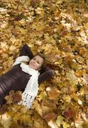 Austria, Female teenager (14-15), relaxing on leaves portrait, elevated view - stock photo