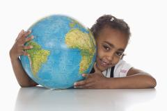 African girl (6-7) holding globe, smiling, portrait Stock Photos