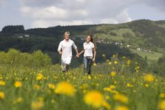 Austria, Young couple walking through meadow - stock photo